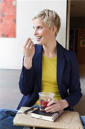 Smiling woman eating salad Stock Photo - Premium Royalty-Free, Code: 649-06532712