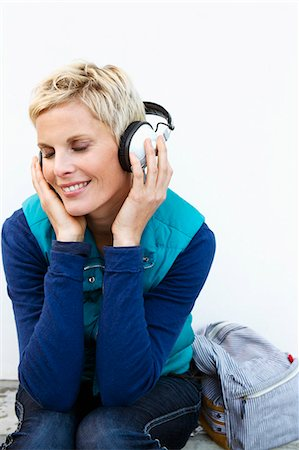 Smiling woman listening to headphones Stock Photo - Premium Royalty-Free, Code: 649-06532726