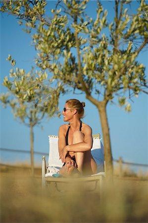 Smiling woman sunbathing outdoors Stock Photo - Premium Royalty-Free, Code: 649-06532797