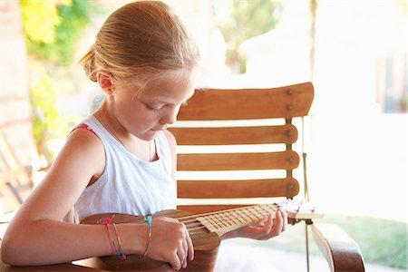 Girl strumming ukulele outdoors Stock Photo - Premium Royalty-Free, Code: 649-06532790