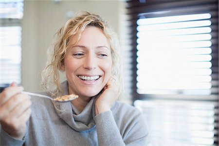 eating - Smiling woman eating cereal indoors Stock Photo - Premium Royalty-Free, Code: 649-06532816