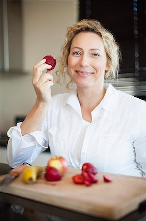 Woman eating fruit in kitchen Stock Photo - Premium Royalty-Free, Code: 649-06532812