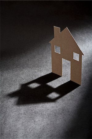 Cardboard house shape casting shadow Stock Photo - Premium Royalty-Free, Code: 649-06532934