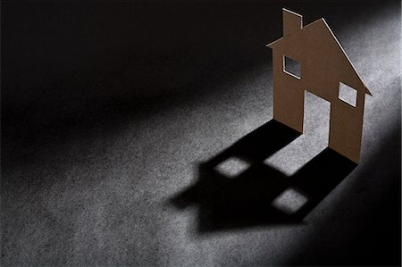 Cardboard house shape casting shadow Stock Photo - Premium Royalty-Free, Code: 649-06532933