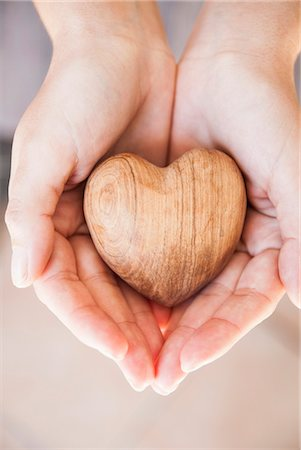 Hands holding carved wood heart Stock Photo - Premium Royalty-Free, Code: 649-06533034