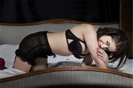 Woman wearing lingerie on bed Stock Photo - Premium Royalty-Free, Code: 649-06533228