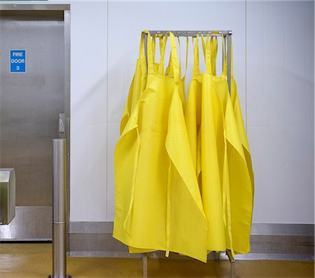 food processing plant - Yellow aprons on drying rack Stock Photo - Premium Royalty-Free, Code: 649-06533396