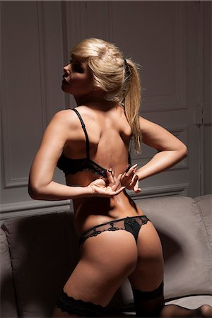Woman in lingerie unhooking her bra Stock Photo - Premium Royalty-Free, Code: 649-06621947