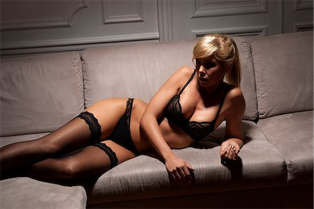 Woman in lingerie laying on sofa Stock Photo - Premium Royalty-Free, Code: 649-06621942