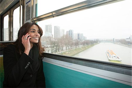 Smiling woman riding train over water Stock Photo - Premium Royalty-Free, Code: 649-06621988