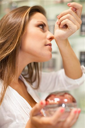 smelling - Woman trying on fragrances in store Stock Photo - Premium Royalty-Free, Code: 649-06622197