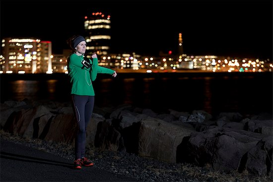Runner stretching on waterfront at night Stock Photo - Premium Royalty-Free, Image code: 649-06622243