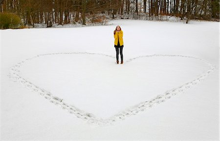 Woman making heart shape in snow Stock Photo - Premium Royalty-Free, Code: 649-06622285