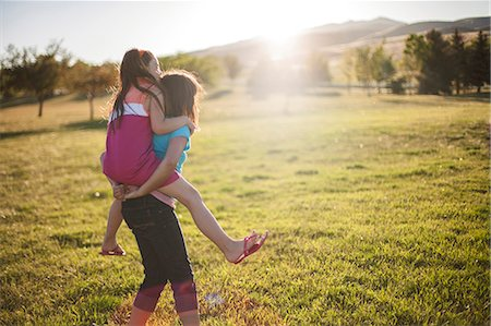 recreational pursuit - Girl carrying friend piggyback in field Stock Photo - Premium Royalty-Free, Code: 649-06622487