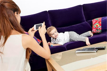 Mother taking picture of son on sofa Stock Photo - Premium Royalty-Free, Code: 649-06622539