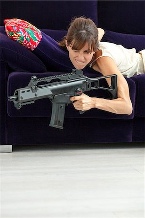 dominant woman - Woman shooting machine gun on sofa Stock Photo - Premium Royalty-Free, Code: 649-06622578