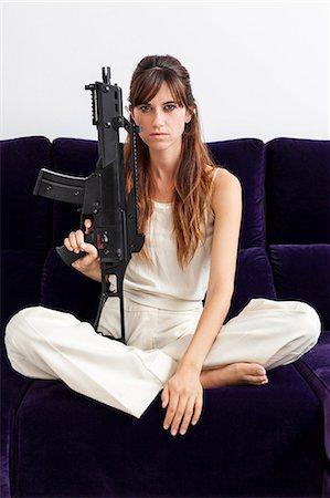 dominant woman - Woman holding machine gun on sofa Stock Photo - Premium Royalty-Free, Code: 649-06622579