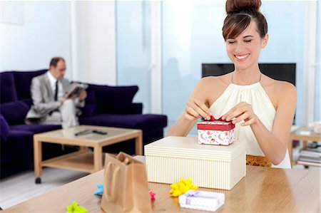 Woman opening presents at table Stock Photo - Premium Royalty-Free, Code: 649-06622573