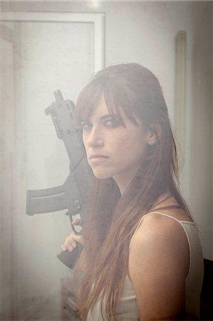 dominant woman - Woman holding machine gun at window Stock Photo - Premium Royalty-Free, Code: 649-06622580