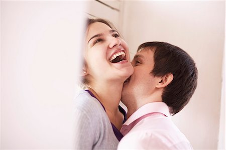 Man kissing girlfriend indoors Stock Photo - Premium Royalty-Free, Code: 649-06622701
