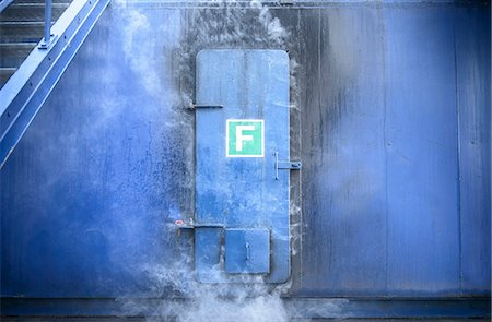 Smoke pouring from behind steel door Stock Photo - Premium Royalty-Free, Code: 649-06622761