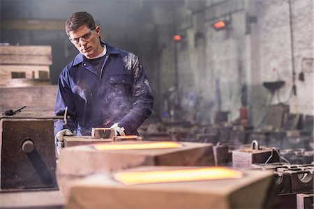 Worker examining moulds in metal foundry Stock Photo - Premium Royalty-Free, Code: 649-06622822
