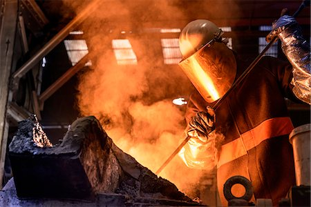 Worker stirring molten metal in foundry Stock Photo - Premium Royalty-Free, Code: 649-06622875