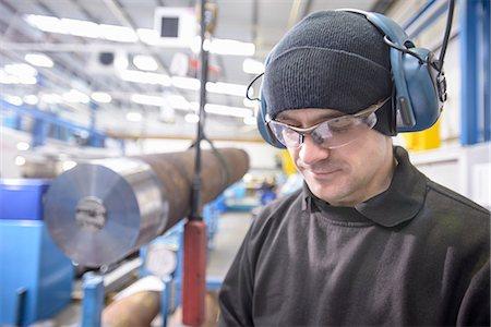 Worker wearing headphones in factory Stock Photo - Premium Royalty-Free, Code: 649-06622902