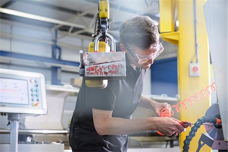 production - Worker using machinery in factory Stock Photo - Premium Royalty-Free, Code: 649-06622943