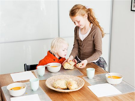 family table eating together - Girl serving brother lunch at table Stock Photo - Premium Royalty-Free, Code: 649-06623058