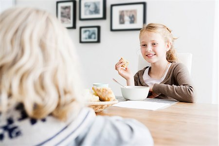 family table eating together - Girls eating lunch at table together Stock Photo - Premium Royalty-Free, Code: 649-06623060