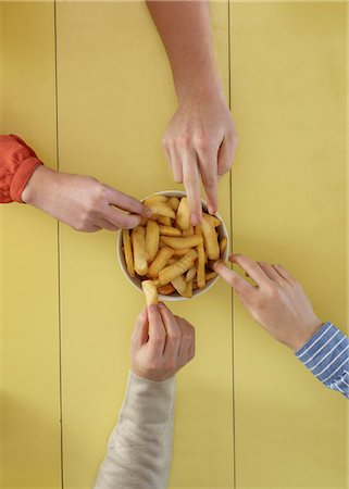reaching - Overhead view of people sharing fries Stock Photo - Premium Royalty-Free, Code: 649-06623174