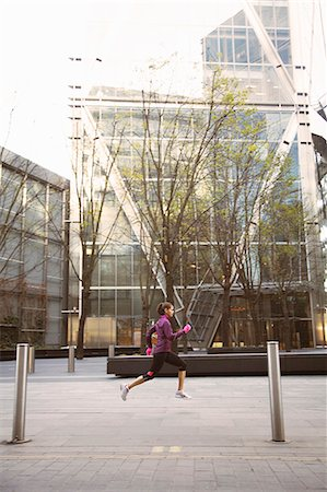 Woman running on city street Stock Photo - Premium Royalty-Free, Code: 649-06716525