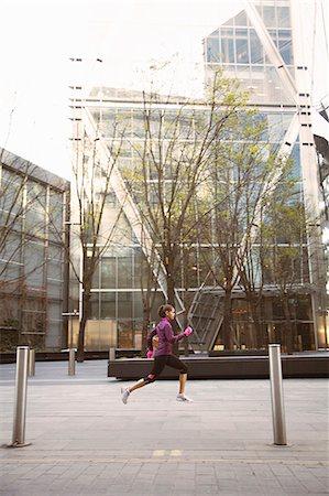 Woman running on city street Stock Photo - Premium Royalty-Free, Code: 649-06716525