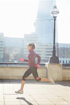 Woman running on urban bridge Stock Photo - Premium Royalty-Free, Code: 649-06716531