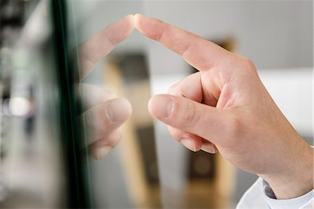 finger - Close up of hand touching glass panel Stock Photo - Premium Royalty-Free, Code: 649-06716719