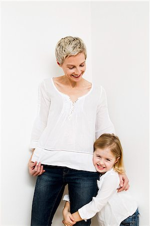 Smiling mother and daughter hugging Stock Photo - Premium Royalty-Free, Code: 649-06716782