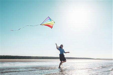 Woman flying kite on beach Stock Photo - Premium Royalty-Free, Code: 649-06716894