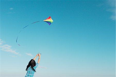 Woman flying kite outdoors Stock Photo - Premium Royalty-Free, Code: 649-06716895