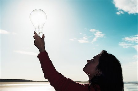 silhouette hand - Woman holding light bulb in sky Stock Photo - Premium Royalty-Free, Code: 649-06716897