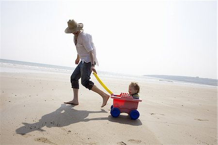 pulling - Father with daughter in wagon on beach Stock Photo - Premium Royalty-Free, Code: 649-06716890