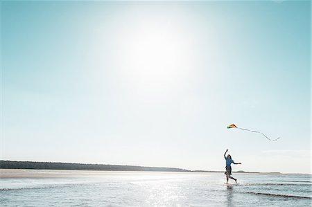 Woman flying kite on beach Stock Photo - Premium Royalty-Free, Code: 649-06716893
