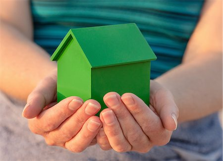 Hands holding model house outdoors Stock Photo - Premium Royalty-Free, Code: 649-06716903