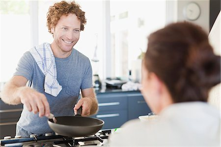 domestic life - Man cooking for girlfriend in kitchen Stock Photo - Premium Royalty-Free, Code: 649-06716953