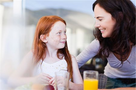 Mother smiling at daughter at breakfast Stock Photo - Premium Royalty-Free, Code: 649-06716963