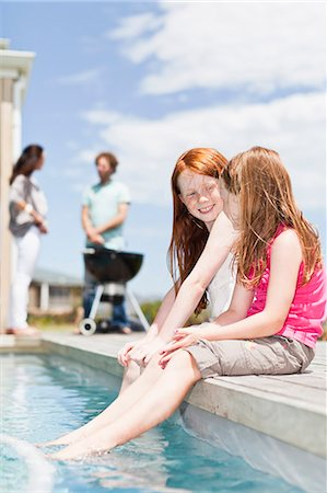 Girls dangling feet in swimming pool Stock Photo - Premium Royalty-Free, Code: 649-06716986