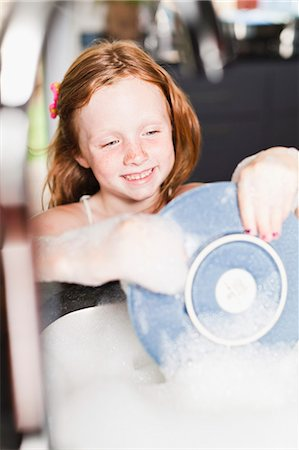 Smiling girl washing plate in sink Stock Photo - Premium Royalty-Free, Code: 649-06716982