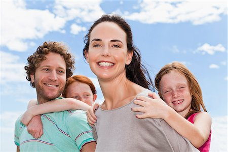 Parents carrying daughters piggyback Stock Photo - Premium Royalty-Free, Code: 649-06716991