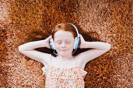 red hair preteen girl - Girl listening to headphones on carpet Stock Photo - Premium Royalty-Free, Code: 649-06717012