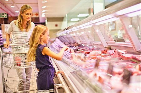 Mother and daughter at butcher counter Stock Photo - Premium Royalty-Free, Code: 649-06717221